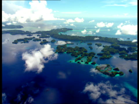 palau's rock islands lie along the coastline in blue water. - palau stock videos & royalty-free footage
