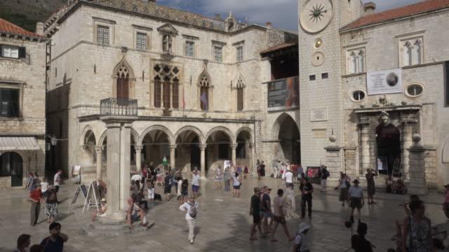 vídeos y material grabado en eventos de stock de pan / palazzo sponza and clock tower at stradun street (placa) and luza square - señal de nombre de calle