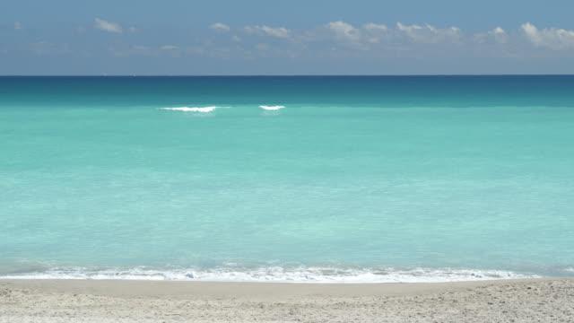 pale blue water lapping on golden sand - atlantik stock-videos und b-roll-filmmaterial