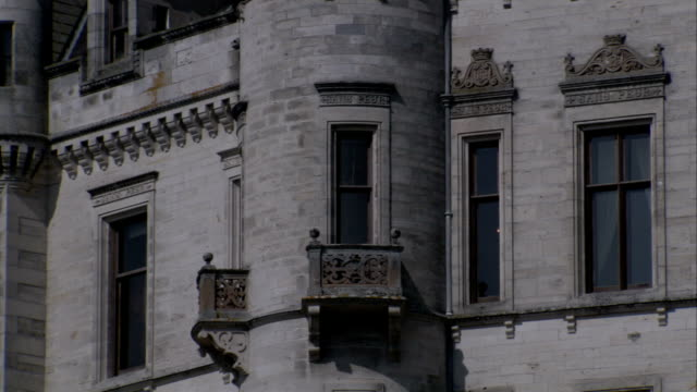 Pale stone and ornate windows characterize the facade of Dunrobin Castle in Sutherland, Scotland. Available in HD.