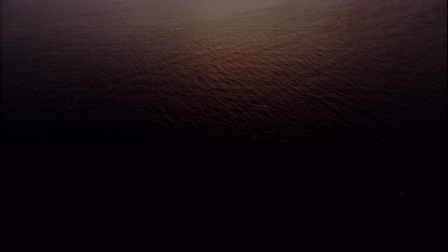Pale sunlight illuminates the Pacific Ocean at sunrise. Available in HD.