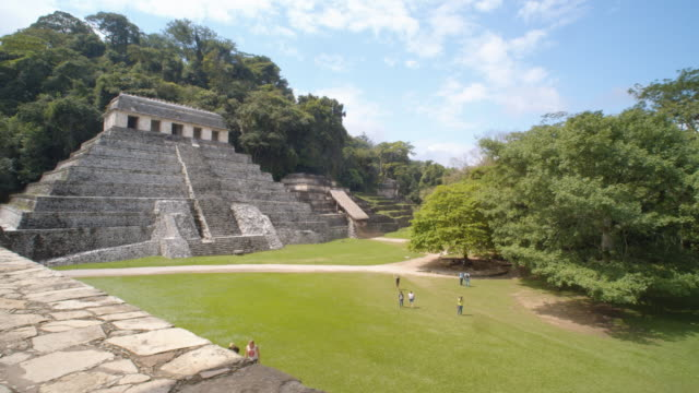 vídeos de stock e filmes b-roll de palenque mayan ruins high angle view establishing shot. pyramid and temple of inscriptions. a few tourist walking along the natural parkland. chiapas, mexico - palenque