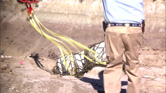 a paleontologist loads dinosaur bones into a net for a helicopter to airlift. - helicopter stock videos & royalty-free footage