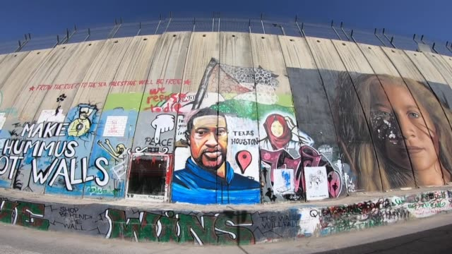 palestinian artist has painted the image of george floyd on the separation barrier, which snakes through the occupied west bank, as a way of protest... - israel stock videos & royalty-free footage