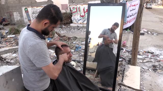 palestinian barber is trying to practice his job on the rubbles of his salon in the blockaded gaze strip which was hit by israeli airstrikes.... - striscia di gaza video stock e b–roll