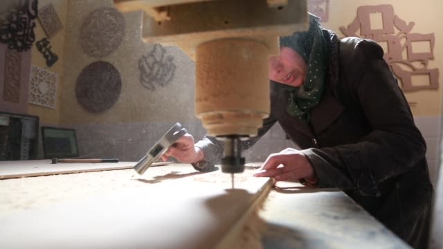 palestinian carpenter smah shaheen works at her workshop in bureij refugee camp in the central gaza strip on march 8 2017 smah shaheen designs... - 国際女性デー点の映像素材/bロール