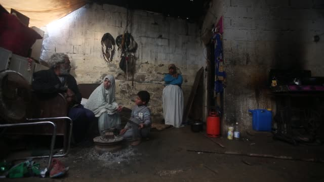 A Palestinian family warms up in front of a fire inside their makeshift house during a cold and rainy weather on the outskirts of Jabaliya refugee...