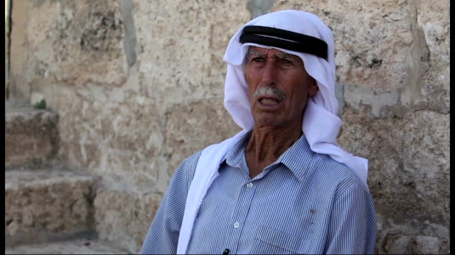 palestinian farmer refuses to sell land israel east jerusalem ext sheep and goats in pen being tended by said eyid high shot of farm buildings and... - 光栄点の映像素材/bロール