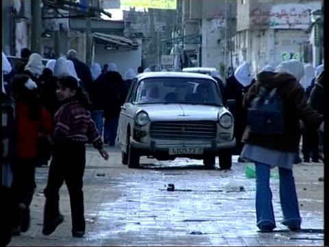 palestinian financial crisis primary school class being taught by woman teacher in islamic dress children sat at desks schoolgirls in islamic... - 女性教師点の映像素材/bロール