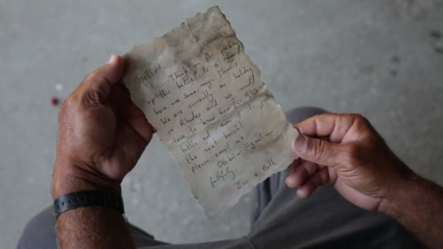 palestinian fisherman jihad alsoltan displays a message in a bottle he found while fishing in the sea on august 212017 the message asks who ever... - messaggio video stock e b–roll