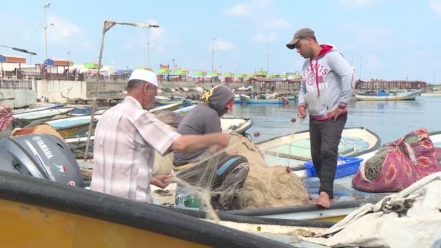 vídeos y material grabado en eventos de stock de palestinian fishermen fix their boats and nets on the beach of gaza city after israel closed the fishing zone off the coast of gaza in retaliation... - venganza