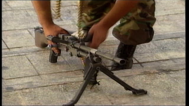 stockvideo's en b-roll-footage met bethlehem palestinian gunmen loading bullets into magazines and preparing weapons ms palestinian police officer greeting gunmen as man pushes camera... - israëlisch palestijns conflict