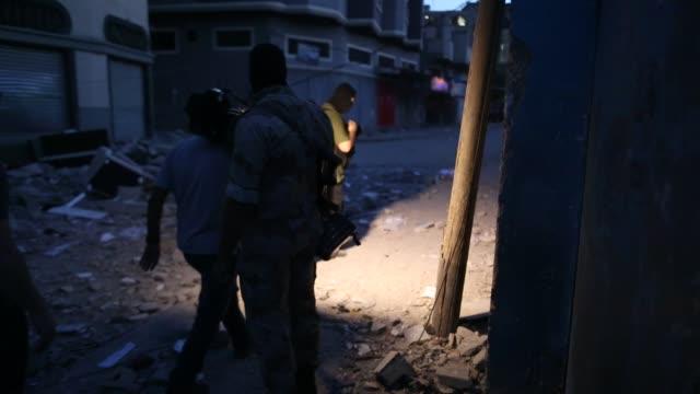 a palestinian islamic jihad militant stands guard at the scene of an israeli strike that killed the group's field commander baha abu alatta in gaza... - jihad stock videos & royalty-free footage
