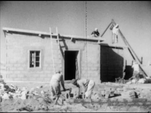 Palestinian male refugees walking down dirt road w/ houses BG MS Bilingual Arabic/English sign VS Male construction workers building block amp mortar...