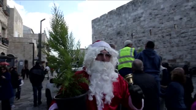 palestinian man dressed up as santa claus was distributing christmas trees along the wall of jerusalems old city on monday as christians around the... - christianity stock videos & royalty-free footage