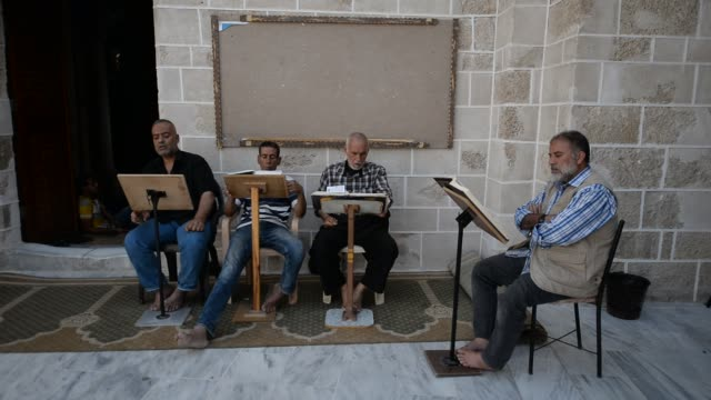 palestinian men read copies of the koran islam's holiest book on the first day of fasting in the muslim holy month of ramadan at the alomari mosque... - holy book stock videos and b-roll footage