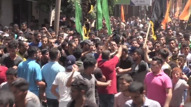 Palestinian mourners carry the bodies of Mohammad Abu Namous Mahmoud AlWalaidah and Mohammed alTaramsi during their funeral in Beit Lahia northern...