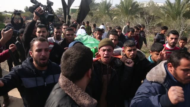palestinian mourners carry the body of amir abu musaid during his funeral in the almaghazi refugee camp in the centre of the gaza strip after he was... - israel palestine conflict stock videos & royalty-free footage