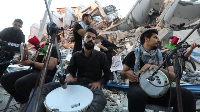 palestinian musicians performed a public concert in front of hanadi apartment which completely destroyed by the israeli army in gaza on wednesday.... - ガザ市点の映像素材/bロール