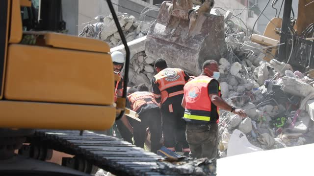 palestinian paramedics search for survivors under the rubble of a destroyed building in gaza city on may 16 following massive israeli bombardment of... - gaza strip stock videos & royalty-free footage