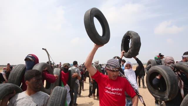 stockvideo's en b-roll-footage met a palestinian protester chants slogans after cutting part of the fence placed by the israeli army during a protest at the gaza strip's border with... - israëlisch palestijns conflict