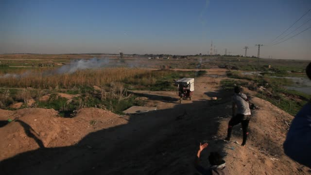 a palestinian protester uses a slingshot to hurl stones towards israeli security forces during clashes near the border between israel and central... - israel palestine conflict stock videos & royalty-free footage