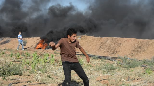 vídeos y material grabado en eventos de stock de a palestinian protester with a slingshot clashes with the israeli security forces during a protest against the israeli blockade at israeli border in... - israel