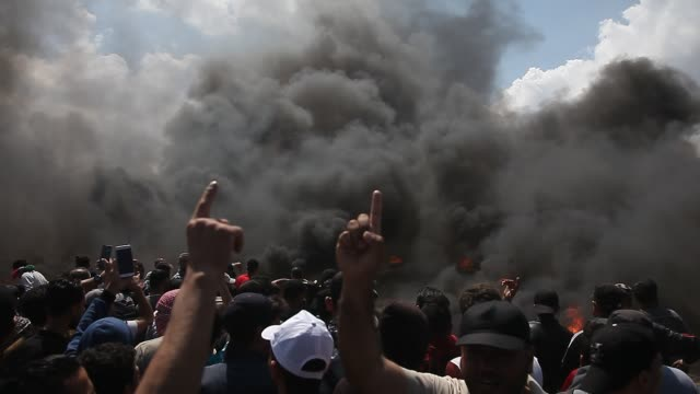 palestinian protesters chant slogans as they burn tires during a protest on the gaza strip's border with israel, monday, may 14, 2018. thousands of... - gaza strip stock videos & royalty-free footage