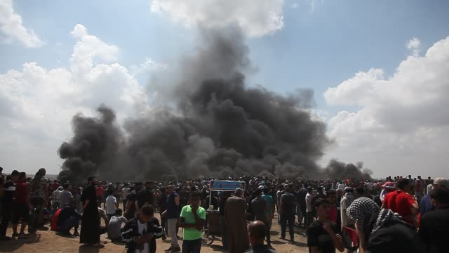 vídeos y material grabado en eventos de stock de palestinian protesters chant slogans as they burn tires during a protest on the gaza strip's border with israel, monday, may 14, 2018. thousands of... - oriente medio