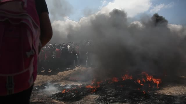 palestinian protesters chant slogans as they burn tires during a protest on the gaza strip's border with israel monday may 14 2018 thousands of... - 2018 gaza border protests stock videos & royalty-free footage