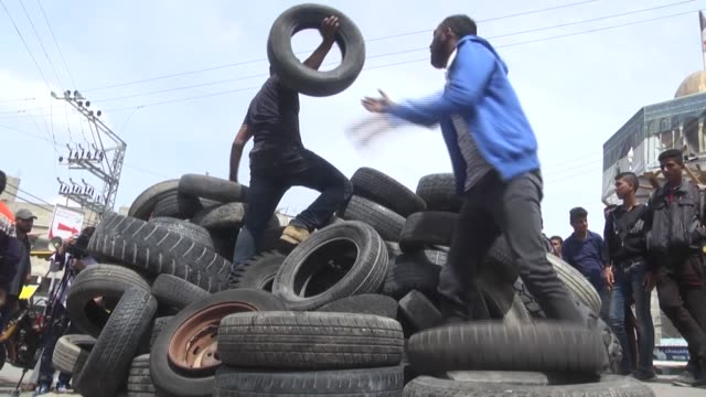 palestinian protesters collect tires to burn during the ongoing protests near the gaza strip's border with israel on april 03, 2018 in khan younis... - 70周年点の映像素材/bロール