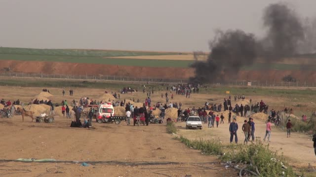 palestinian protesters gather in front of burned tires while israeli soldiers fire tear gas during clashes with israeli troops along gaza's border... - israel palestine conflict stock videos and b-roll footage