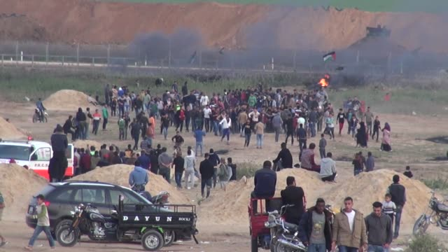 Palestinian protesters gather in front of burned tires while Israeli soldiers fire tear gas during clashes with Israeli troops along Gaza's border...