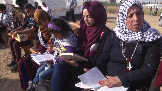 Palestinian protesters read books as a reaction during a demonstration demanding the right of return and removal of the blockade following the 'Great...