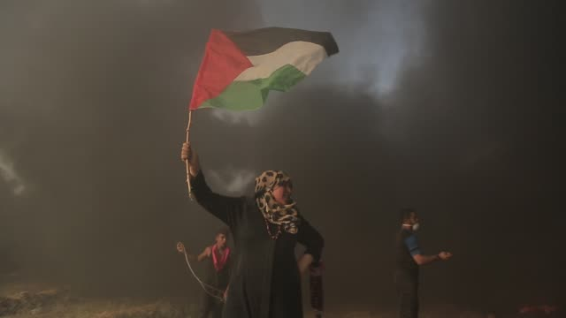 palestinian protesters set tires on fire in response to israeli forces' intervention in the 24th friday of great march of return demonstration near... - israel palestine conflict stock videos and b-roll footage