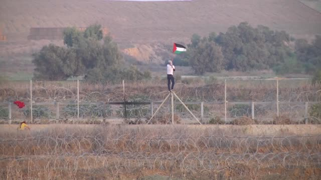 palestinian protesters throw a tear gas canister back at israeli soldiers on gaza border near the al-bureij refugee camp during a protest against the... - refugee stock videos & royalty-free footage