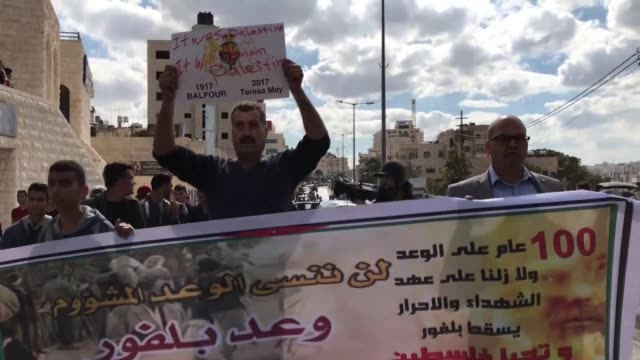 Palestinian protesters throw shoes to a puppet depicting Arthur Balfour British and Israeli flags during a protest in the West Bank city of Ramallah...
