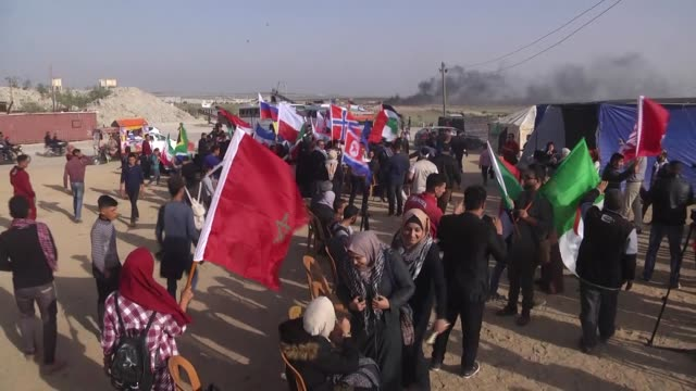 palestinian protesters wave many countries' flag during a demonstration demanding the right of return and removal of the blockade following the... - ガザ市点の映像素材/bロール