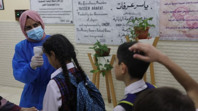 palestinian staff member checks a student temperature in the rosary sisters school gaza , on the first day of a new school year, as palestinians ease... - worry beads stock videos & royalty-free footage
