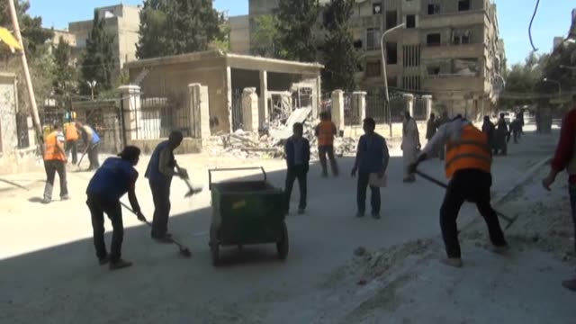 Palestinian volunteers sheltering at Yarmouk Refugee Camp in Damascus clean the streets of the camp within a campaign started to remove the debris of...
