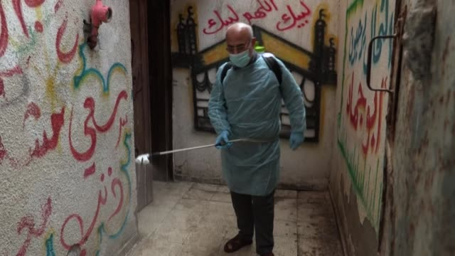 palestinian volunteers spray disinfectant in the streets of the al-shati refugee camp in gaza city, during a campaign by hamas to stem the novel... - gaza strip stock videos & royalty-free footage