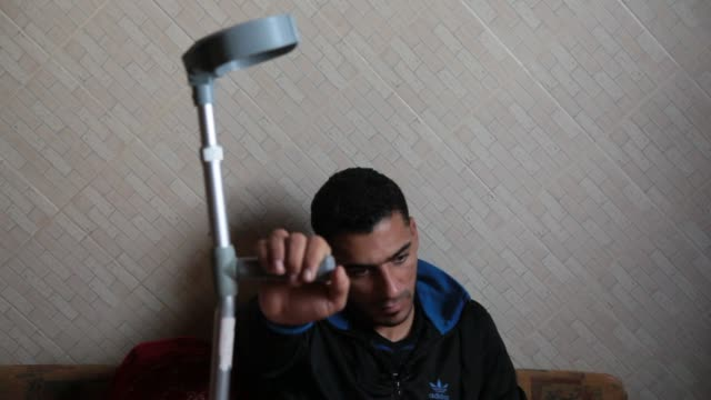 palestinian wael alnamla who was injured during the 50day war between israel and hamas militants in the summer of 2014 lies on the sofa at his house... - israel palestine conflict stock videos and b-roll footage
