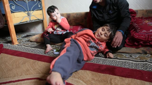 palestinian wael alnamla who was injured during the 50day war between israel and hamas militants in the summer of 2014 lies on the sofa at his house... - israel palestine conflict stock videos & royalty-free footage