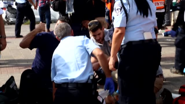 stockvideo's en b-roll-footage met palestinian who allegedly slightly injured a policeman by stabbing is seen on the ground after he was shot by an israeli policewoman in east... - oost jeruzalem