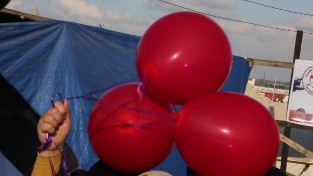 palestinian women holds balloons during a tent city protest at the israelgaza border in the southern gaza strip april 10 2018 - israel palestine conflict stock videos and b-roll footage