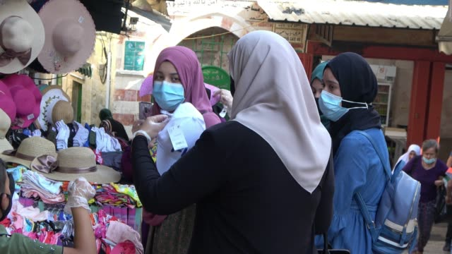 palestinian women wearing protective mask due to the coronavirus pandemic buying hats on august 28, 2020 in the old city of jerusalem, israel.... - old town stock videos & royalty-free footage