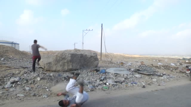 Palestinian youth practices parkour skills amid the ruins of buildings which were destroyed by Israeli offensives in Beit Lahia town of Gaza on...
