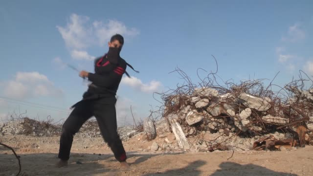 Palestinian youths fight with swords as they demonstrate their ninjastyle skills near the buildings destroyed by the Israeli attacks in 2014 in Beit...