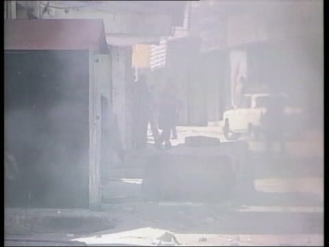 stockvideo's en b-roll-footage met palestinian youths throwing stones at israeli security forces israeli soldier firing youths scattering - israëlisch palestijns conflict