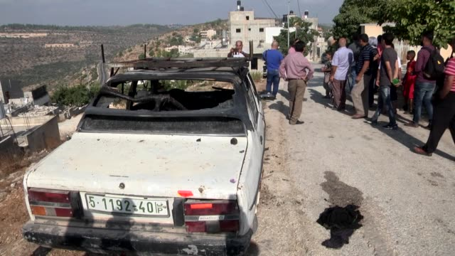 Palestinians and Israeli security officials inspect a car which was burnt by Israeli settlers in Umm Safa village of Ramallah in the occupied West...